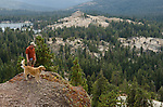 A hiker and his dog take in the view from a rock outcropping, Sierra Nevada, Toiyabe National Forest, California