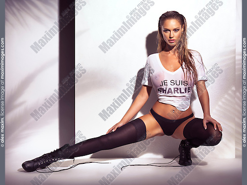 Sexy young glamourous woman with wet blond hair wearing a wet Je Suis Charlie shirt, underwear and black stockings with boots on white background.