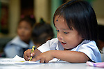 """In the capital of the Philippines, a girl who lives in the Manila North Cemetery enjoys drawing in class at the nearby Santa Mesa Heights United Methodist Church. Hundreds of poor families live in the cemetery, inside and between the tombs and mausoleums of the city's wealthy. They are often discriminated against, and many of their children don't go to school because they're too hungry to study and they're often called """"vampires"""" by their classmates. With support from United Methodist Women, KKFI provides classroom education and meals to kids from the cemetery at this church."""