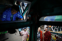 """Buddhist monks are seen through the window as Khin Aung, the driver of legendary """"Bayboo"""" bus stops to pick-up passengers in central Yangon September 23, 2012. On the line 61, several ÒBaybooÓ buses take passengers from the North Dagon Township to the city. Possibly the oldest operating bus in the world, ÒBaybooÓ (big belly in Burmese language) is an improvised legend that maneuvers dirty roads for over 70 years. The original vehicle, of which only charm of its spectacular ugliness.is still visible, was WWII military Chevrolet C15. Modified to serve.public transportation, these ancient vehicles that would be banned by.law in almost any other country are great proof what MyanmarÕs.transportation is today.    REUTERS/Damir Sagolj (MYANMAR)"""