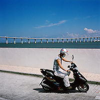 A scooter driving near the seafront with one of Macau's bridges in the background..