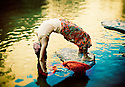 Yoga Woman outdoors in yoga pose urdhva dhanurasana in a colorful pond.