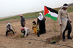 Palestinians dressed up as farmers plant trees as they take part in a rally marking Land Day in Beit Hanun in the northern Gaza Strip close to the border with Israel on March 31, 2013. The annual demonstrations mark the deaths of six Arab Israeli protesters at the hands of Israeli police and troops during mass protests in 1976 against plans to confiscate Arab land in the northern Galilee region. Photo by Ashraf Amra