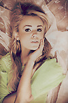 blonde hair lady in green blouse with lace, lying on tulle material looking at camera