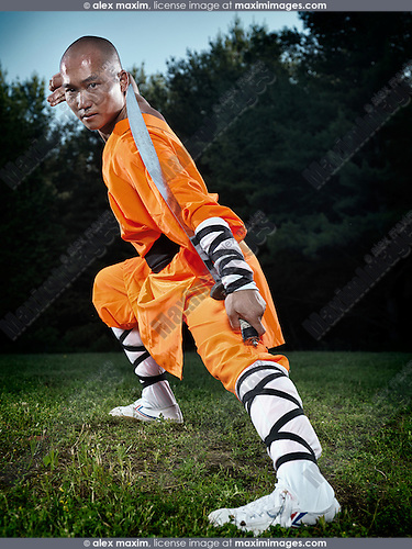 Dramatic portrait of a Shaolin warrior monk with a broad sword outdoors