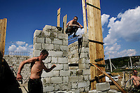 Workmen construct a shop in the village of Tataresi.