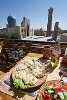 Uzbekistan, Bukhara.<br /> Traditional Manty (steamed dumplings) in  a restaurant overlooking Kalon Minaret (r.) and Mir-i-Arab Medressa.