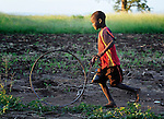 "A boy playing with a wheel in Dickson, a village in southern Malawi that has been hard hit by drought in recent years, leading to chronic food insecurity, especially during the ""hunger season,"" when farmers are waiting for the harvest."