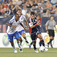 New England Revolution midfielder Benny Feilhaber (22) brings the ball forward as Montreal Impact midfielder Collen Warner (18) defends. In a Major League Soccer (MLS) match, Montreal Impact defeated the New England Revolution, 1-0, at Gillette Stadium on August 12, 2012.