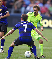Seattle Sounders FC forward Roger Levesque tries to get around Manchester United forward Michael Owen during play at CenturyLink Field in Seattle Wednesday July 20, 2011. Manchester United won the match 7-0.