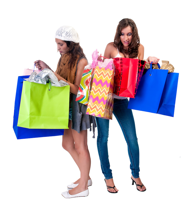 Young caucasian and hispanic girls looking at shopping bags very interested.