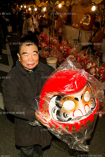 A man shows a huge Daruma doll outside the Shorinzan Daruma Temple in Takasaki City, Gunma Prefecture on January 6, 2016, Japan. Every year thousands of people visit the country's most famous Daruma market (Daruma ichi) held at the Shorinzan Daruma Temple on January 6 and 7. Takasaki City, is known as the capital of Daruma dolls and about 80% of Japan's Daruma are produced there. According to the tradition, Daruma dolls are sold without pupils painted on their eyes. People color in one pupil when a wish is made or a goal set, and when the wish comes true or the goal is achieved they fill in the other pupil. At the end of the year, used Daruma dolls are returned to the temple to be burned. (Photo by Rodrigo Reyes Marin/AFLO)