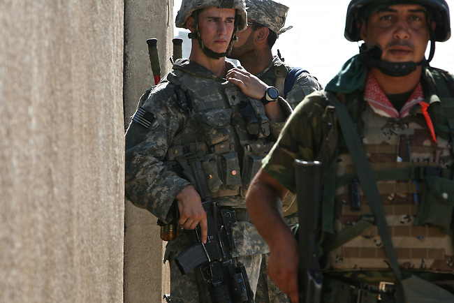 Spc. Sean Wilson, 21, of Jacksonville, Fla., of Company C, 1st Battalion, 23rd Infantry Regiment and an Iraqi soldier stand guard outside a house in Baqubah, Iraq, as other troops search for insurgents and weapons. Resident say most fighters fled the city two days before U.S. and Iraqi forces arrived. June 25, 2007. DREW BROWN/STARS AND STRIPES