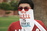 """Phoenix, Arizona (July 28, 2012) - About three hundred people marched to protest the second anniversary of the approval of some provisions of the SB 1070 immigration law. The march, called """"No Papers, No Fear"""" was organized by immigrant rights groups who say the law discriminates people of brown skin. In this photograph, a young man who participated in the """"No Papers No Fear"""" march wears a bandana to cover part of his face. The message printed in the bandana read: """"No Human Is Illegal"""".  The march was held to oppose Arizona immigration law SB 1070 and racial profiling. Photo by Eduardo Barraza © 2012"""