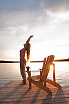 Woman stretching on a dock by Clear Lake.  A chair and coffee cup are on the dock in the early morning light that is back lighting her long blond hair.  Yoga pose. Riding Mountain National Park, Manitoba, Canada