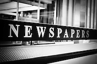 Black and white photo of Chicago newspapers stand sign on a self service coin operated news kiosk in downtown Chicago, Illinois, USA.