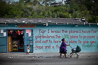 Street scene. Nauruans are fervent Christian believer. Nauru, officially the Republic of Nauru is an island nation in Micronesia in the South Pacific.  Nauru was declared independent in 1968 and it is the world's smallest independent republic, covering just 21square kilometers..Nauru is a phosphate rock island and its economy depends almost entirely on the phosphate deposits that originate from the droppings of sea birds. Following its exploitation it briefly boasted the highest per-capita income enjoyed by any sovereign state in the world during the late 1960s and early 1970s..In the 1990s, when the phosphate reserves were partly exhausted the government resorted to unusual measures. Nauru briefly became a tax haven and illegal money laundering centre. From 2001 to 2008, it accepted aid from the Australian government in exchange for housing a Nauru detention centre, with refugees from various countries including Afghanistan and Iraq..Most necessities are imported on the island..Nauru has parliamentary system of government. It had 17 changes of administration between 1989 and 2003. In December 2007, former weight lifting medallist Marcus Stephen became the President.