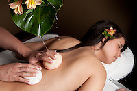 A young adult woman receives a massage with shells. *Model and property release available*