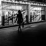 Silhouette of female figure walking alone along street in Canada