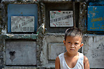 """A boy in the Manila North Cemetery. Hundreds of poor families live here, dwelling in and between the tombs and mausoleums of the city's wealthy. They are often discriminated against, and many of their children don't go to school because they're too hungry to study and they're often called """"vampires"""" by their classmates. With support from United Methodist Women, KKFI provides classroom education and meals to kids from the cemetery at a nearby United Methodist Church."""