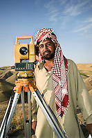 A surveyor, wearing a bright red keffiyeh, uses a theodolite to measure the route of a road being constructed between Mazar-e-Sharif (Balkh Province) and Darae Souf (Samangan Province)..