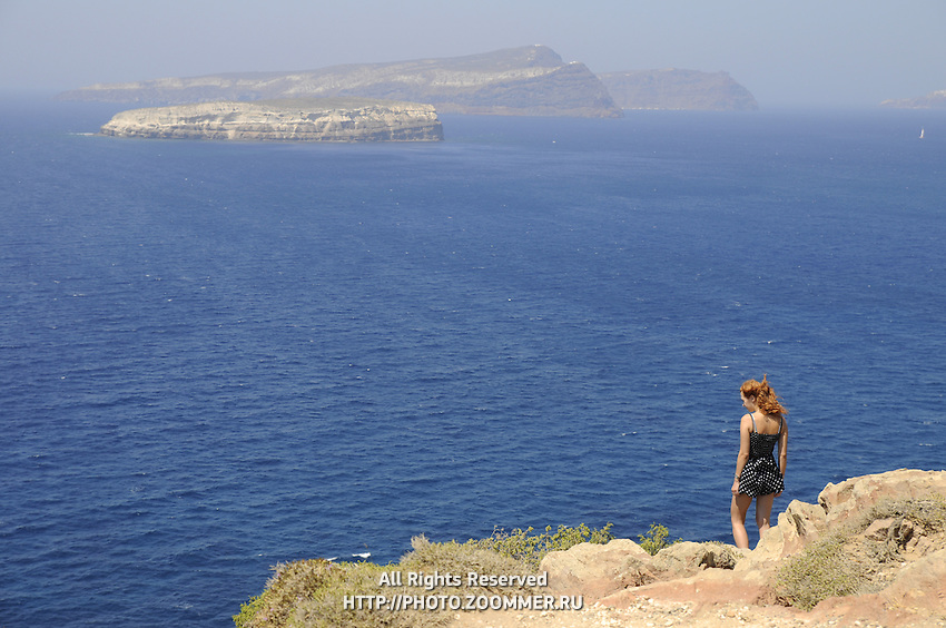 Girl on cliff looking far to the sea and volcano caldera in Santorini