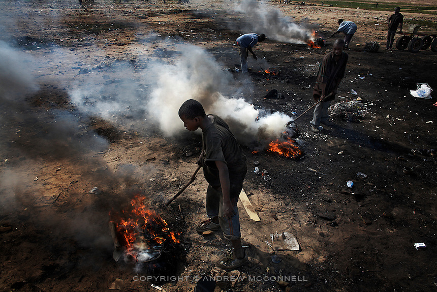 Children burn cables from computers and other electronic equipment in order to retrieve copper, at Agbogbloshie dump, in Accra, Ghana. Combustion releases toxic metals such as lead, beryllium, cadmium and mercury into the atmosphere. At theses burning sites concentrations of toxic metals have been found at over one hundred times the normal level. Children do not wear any protective clothing and so expose themselves to lethal doses of these hazardous chemicals.