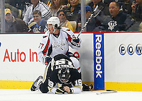 T.J. Oshie #77 of the Washington Capitals hits Beau Bennett #19 of the Pittsburgh Penguins along the boards in the first period during the game at Consol Energy Center in Pittsburgh, Pennsylvania on December 14, 2015. (Photo by Jared Wickerham / DKPS)