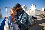 RENO, NV - OCTOBER 6:  Billy Blanton, right, embraces friend Marian Schamp in a tent city for the homeless in downtown Reno, Nevada October 6, 2008. The City of Reno set up the tent city when existing shelters became overcrowded as Nevada struggles with one of the highest unemployment rates in the country. (Photo by Max Whittaker/Getty Images)
