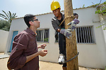Teacher Mohammed Alatrush (left) instructs student Emad Abu Holli in pole-climbing technique in a class on electrical wiring at the Vocational Training Center in Khan Yunis, Gaza. The center is sponsored by the Department of Service for Palestinian Refugees of the Near East Council of Churches, and funded in part by the Pontifical Mission for Palestine. DSPR is a member of the ACT Alliance.