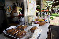 A young woman works behind the counter featuring Aunty Sandy's banana bread at the Ke'anae Fruit Stand along the Hana Highway, Ke'anae Peninsula, Maui.