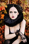 A girl with pale skin, gothic styling and heavy make-up sitting in an autumnal setting and looking at the camera.