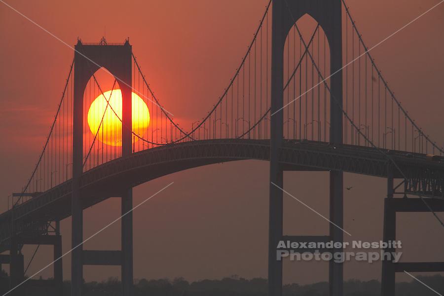 USA, Newport, RI - Sunset behind pilings of Newport Bridge.