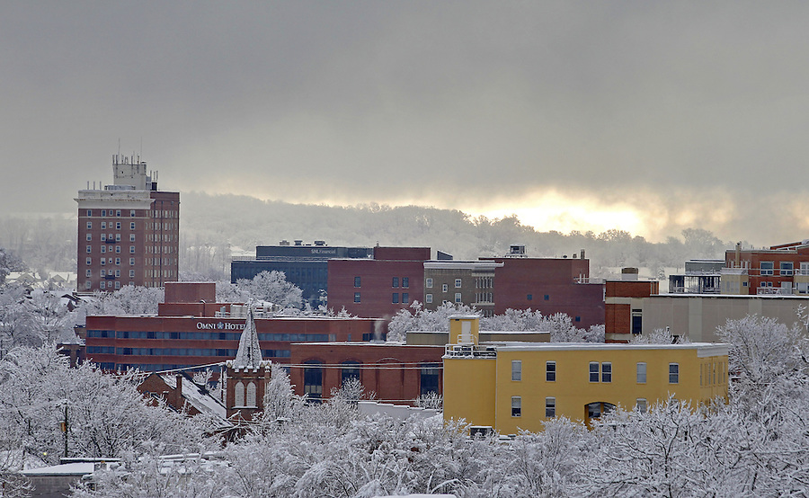 Early morning light appears behind a snow covered Downtown Charlottesville, VA. Photo/Andrew Shurtleff