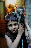 Ravi a  madari boy(who shows trick with animals) with his monkey at Katputly colony in New Delhi, India. 14.11.2009. Kathputly colony is a slum area in West Delhi. This slum seems like any other slum areas of modern India with dysfunctional electricity, non existing sanitation and poverty. As a part of Delhi, this is also ailed with water crisis. Large families live their lives crammed together in a single room with all the odds which complement poverty. One thing which differentiates this slum with any other is the people living in the colony. Nearly everybody in this slum is a traditional performing artist; and they have been migrating to this area for last 50 years from different parts of the country for a better livelihood. They are magicians, acrobats, jugglers, puppeteers, dancers and musicians. These artistes perform in star rated hotels, marriage ceremonies of the richer section, functions, and festivities all around the country and the world. Most of the artisans I met here, have performed in Europe and America but such opportunities are rare to come by. They struggle to keep their art form alive. They say that they don't get any help or support from the government for their basic needs and for the well being of the Kathputly colony -  though they have uphold the prestige of the country internationally. Polluted air, dirty alleys smelling of urine, colourful dress and sound of music characterise Kathputly colony, which is the one of its kind in India. Arindam Mukherjee