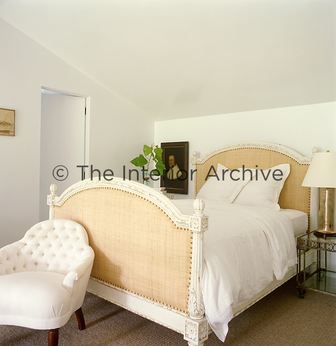 The small bedroom is furnished with an antique bed upholstered in beige henp and a button-back chair covered in contemporary linen