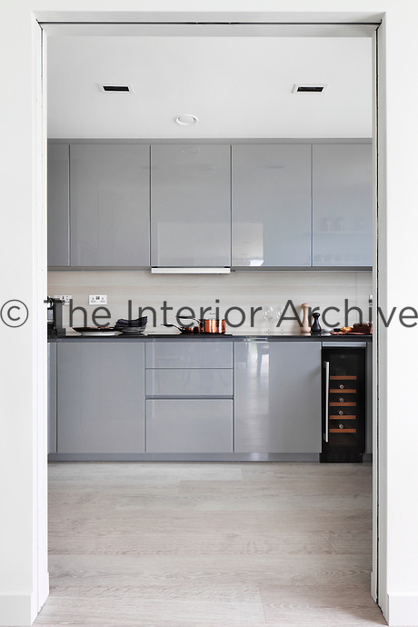 A view through an open doorway to a modern kitchen with glossy grey units.