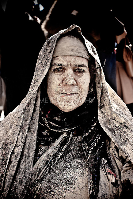 KHORRAMABAD, IRAN : A woman covered in mud during the festival of Ashura...Every year to mark the death of Imam Hussein, Shia Muslims mourn for two days. In Khorramabad and Lorestan in the west of Iran, during the first day of mourning, called Tasooa, women take a vow of silence and go through the streets with the children lighting candles. At 4 am on Ashura, the second day, men cover themselves in mud and then stand in front of a fire until the mud has dried to clay. After this they go to the mosque and pray...Photo by Farhad Babaei/Metrography