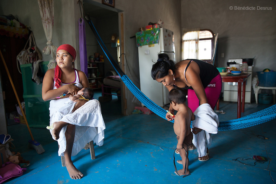 "Luz Betsaida Orozco Pineda (L) and her new born baby at their home in Juchitán, Mexico on February 17, 2016. Now 14, Luz became pregnant when she was 13 after being ""stolen"" according to the Zapotec Indigenous tradition. Considered a traditional kind of marriage – Luz is too young to wed legally – the custom dictates that the couple go to the young man's house and announce their plans to marry. While the family waits, the couple go to a room together; he emerges later with a blood-stained handkerchief to prove his bride's virginity. Luz, who started going out with the father of her baby when she was 10, lives with her in-laws in the 6 de noviembre neighbourhood on the outskirts of Juchitán in the southern Mexican state of Oaxaca. Her baby was born on January 13, 2016. Despite following tradition, she speaks little Zapotec – the language of her husband and his family – she follows tradition, wearing a headscarf to protect her health as she is still observing the 40-days quarantine period after giving birth, during which she stays in the house. While Mexico has outlawed marriage under the age of 18, many young girls become unofficial wives and mothers much earlier. In Juchitán, teenage pregnancy is expected, even prized. Mexico ranks first in teenage pregnancies among the member countries of the Organization for Economic Co-operation and Development (OECD). Photo by Bénédicte Desrus"