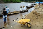 Bolivia,  Trinidad, a common job for men is shoveling sand from the river for use in the construction industry. Each full truck  earns the men a share of $25 and they fill about 3-5 per day.