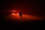 A firefighter is silhouetted against color and smoke as wildfire rages in Running Springs near Lake Arrowhead early Tuesday morning October 23, 2007.