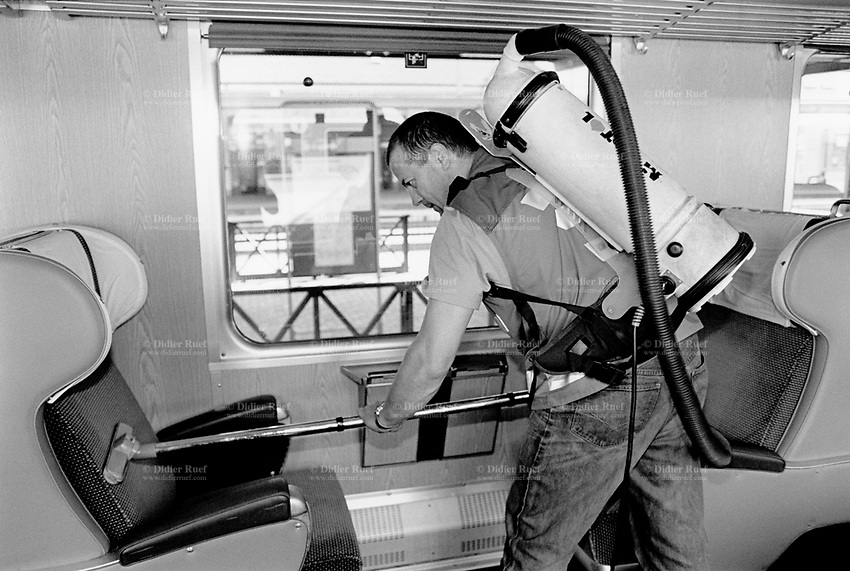 Switzerland. Chiasso. Railway station. Train's car.  A worker cleans the first class velvet seats with a hoover which he carries on his back.  © 1998 Didier Ruef