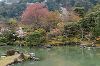 Trees cover the banks of the ornamental lake in the garden at Tenryu-ji Temple, Kyoto