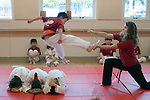 Albany CA Mixed-age class of children at Tae Quan Do demonstration, showing how to leap over crouching bodies and break a board with a kick