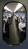 Passengers sleep in Shinkansen, or bullet train, on departure from Kyoto to Tokyo, Japan, on November 10, 2006. Photo by Lucas Schifres/Pictobank