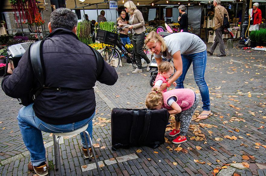Nederland, Utrecht, 27 sept 2014<br /> Kindje kijkt in de tas van accordeonspeler hoeveel geld daar al in zit. Accordeonspeler op bloemenmarkt speelt voor geld <br /> Foto: (c) Michiel Wijnbergh