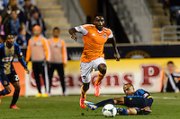 Warren Creavalle (5) of the Houston Dynamo jumps over the tackle of Fabio Alves (Fabinho) (33) of the Philadelphia Union. The Houston Dynamo defeated the Philadelphia Union 1-0 during a Major League Soccer (MLS) match at PPL Park in Chester, PA, on September 14, 2013.