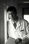 b/w serious, portrait of concerned looking doctor in hospital corridor