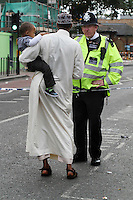 A policeman talks to a person holding a child after a riot in Tottenham. London saw the beginnings of riots on Saturday evening, after a peaceful protest in response to the shooting by police of Mark Duggan during an attempted arrest, escalated into violence. By the third night of violence, rioting and looting had spread to many areas of the capital and to other cities around the country.