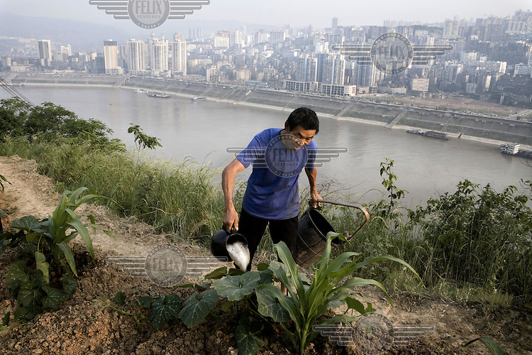 Farmer Huang Gingshi watering his crops in a field above the Yangtze Riverand the city of Fuling (in the background).